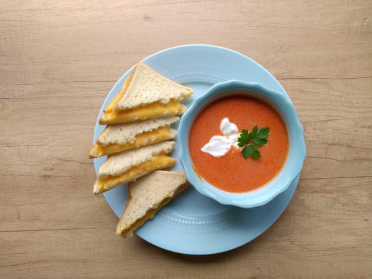 kremowa zupa pomidorowa podana w miseczce w towarzystwie serowych tostów po amerykańsku