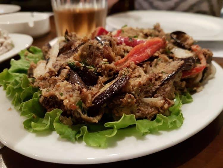 Jedzenie kuchni gruzińskiej z kaszą i sałatą na białym tależu