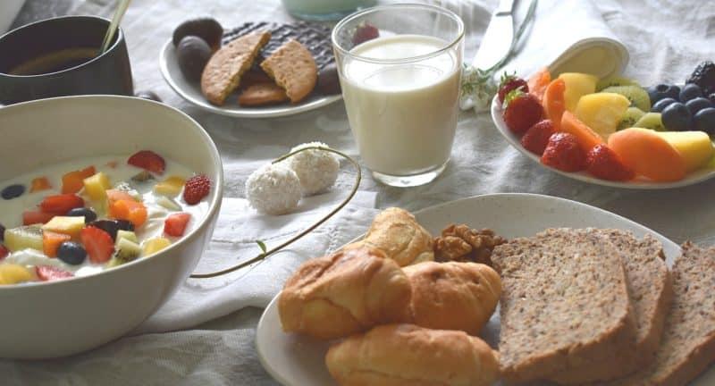 Kefir w szkloance na śniadanie z bułeczkami i płatkami
