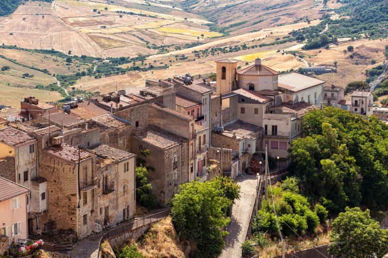 Widok na dolinę na Sycylii. Stare kamienne domki a w tle winorośla